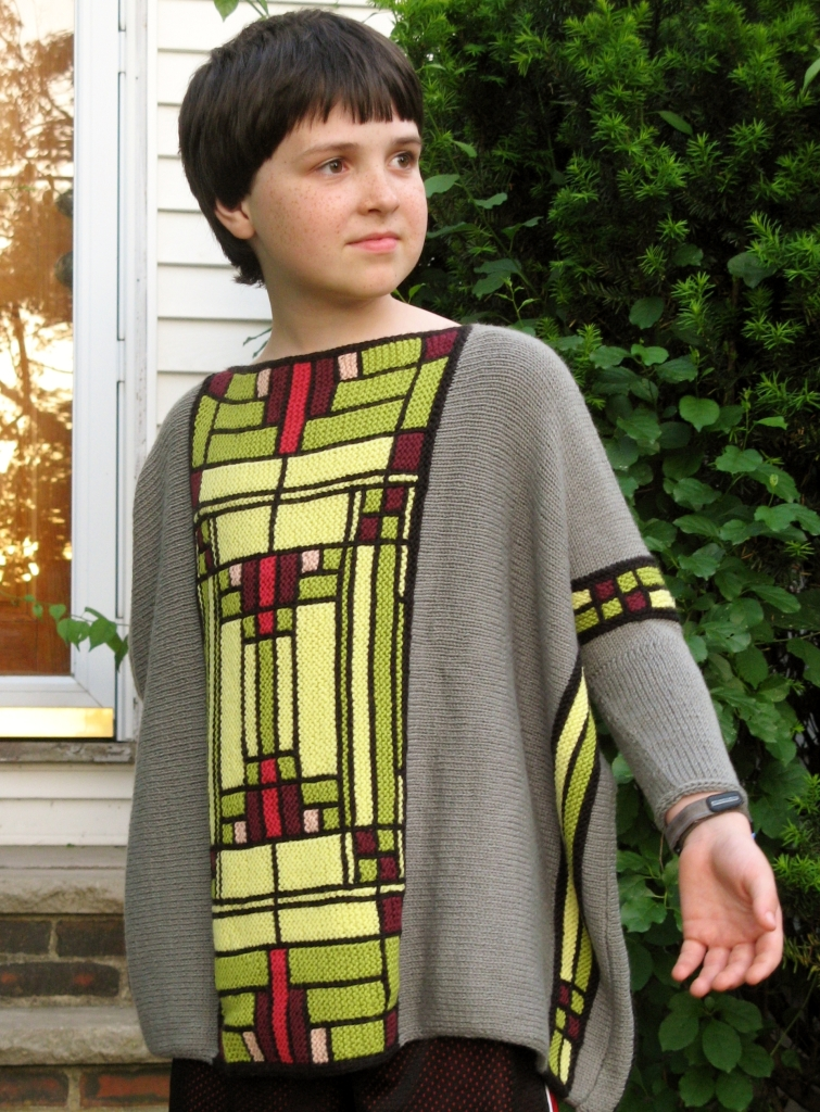 "a young person models a mostly-grey sweater with a long ""stained glass"" panel down the front; pattern resembles stained glass motifs from Frank Lloyd Wright"